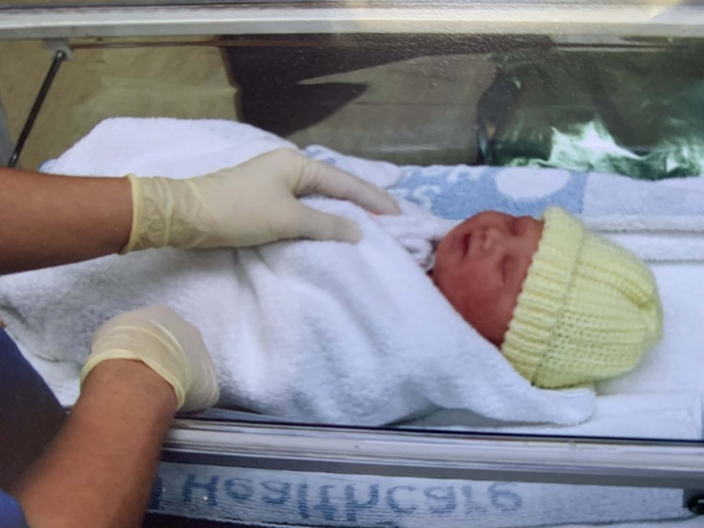 newborn baby in a hospital cot